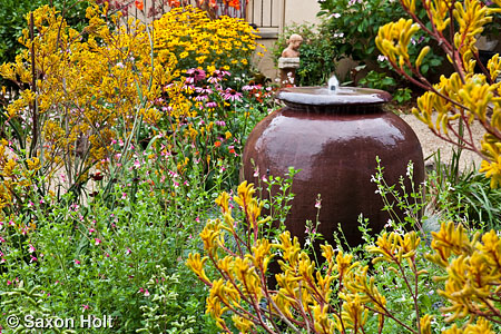 Urn fountain as focal point in perennial garden with yellow Kangaroo paw