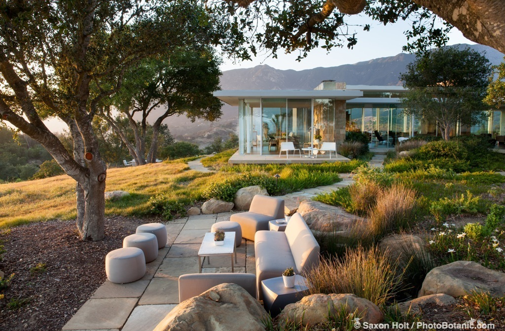 Outdoor stone patio sitting area under Oaks next to modern glass hilltop home with California native plant garden, Santa Barbara,